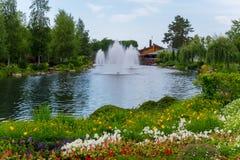 Uma variedade magnífica de crescimento de flores na costa de uma lagoa com fontes Fotografia de Stock Royalty Free