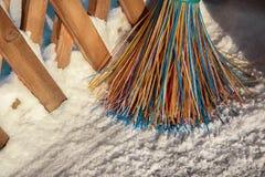 Uma vassoura plástica com as cerdas coloridos dos suportes da pilha na neve O conceito de limpar a área da neve no inverno foto de stock royalty free