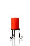 Uma vela alaranjada em um suporte preto. Fotos de Stock Royalty Free