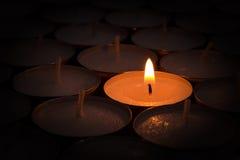 Uma vela ardente ilumina outro Foto de Stock