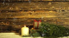 Uma vela ardente, um ramo da pele-árvore e caixas de presente em um fundo do drevisny escovado vídeos de arquivo