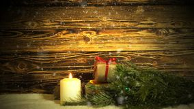 Uma vela ardente, um ramo da pele-árvore e caixas de presente em um fundo do drevisny escovado filme