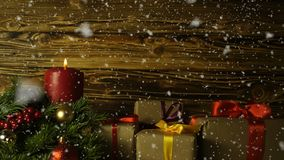 Uma vela ardente, um ramo da pele-árvore e caixas de presente em um fundo do drevisny escovado video estoque