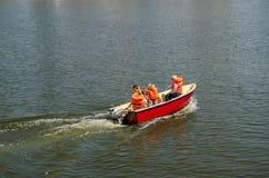 Uma vela da família em um barco em revestimentos de vida alaranjados Rio em Wroclaw imagem de stock
