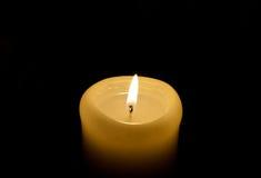 Uma vela ilumina-se acima na escuridão Fotografia de Stock