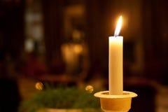 Uma vela iluminada em uma tabela Fotos de Stock Royalty Free
