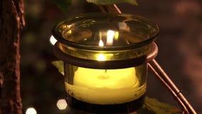 Uma vela iluminada queima-se lentamente em uma bacia verde no templo video estoque