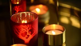 Uma vela que queima-se em um casti?al vermelho Sentimento do calor e do conforto filme