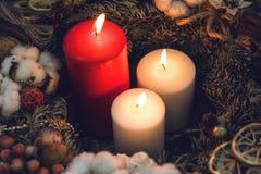 Uma velas ardentes vermelha e duas branca em uma grinalda Fotografia de Stock Royalty Free