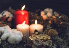 Uma velas vermelha e duas branca em uma grinalda Imagem de Stock Royalty Free