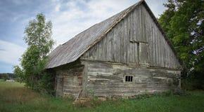 Uma vertente de madeira abandonada velha com um telhado da ardósia na vila imagem de stock