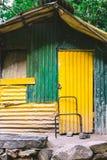Uma vertente ou uma barraca feita de ferro ondulado pintaram o verde e o amarelo fotografia de stock royalty free