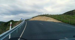Uma viagem ao longo de uma estrada de enrolamento através dos montes perto da costa com rochas filme