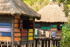 Uma vila colorida do pernas de pau na flutuação de África. Imagens de Stock