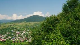 Uma vila perto do rio Na perspectiva das montanhas cobertas com a estância de esqui da floresta no verão, resto no video estoque