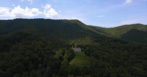 Uma vista aérea da casa na floresta durante o verão, com uma mistura de árvores sempre-verdes com montanhas bonitas no filme