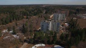 Uma vista aérea de construções residenciais em uma área arborizada em um dia brilhante filme