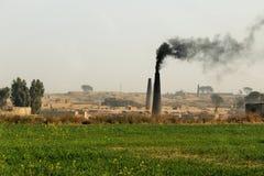 Uma vista da estufa de tijolo que emite-se o fumo fotografia de stock royalty free
