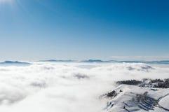 Uma vista da parte superior de uma montanha nevado a um vale coberto por uma névoa em um dia ensolarado com um céu azul claro imagens de stock