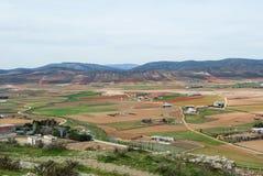 Uma vista da plataforma de observação aos campos, às explorações agrícolas e às montanhas perto da cidade no dia nebuloso da mola Imagem de Stock
