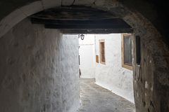 Uma vista de uma rua estreita com arco e as janelas de madeira e as portas com parede branca apedrejam a arquitetura da ilha Patm Imagem de Stock Royalty Free
