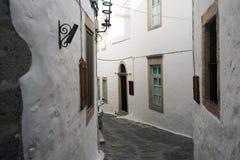 Uma vista de uma rua estreita com arco e as janelas de madeira e as portas com parede branca apedrejam a arquitetura da ilha Patm Foto de Stock Royalty Free