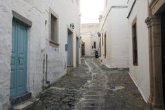 Uma vista de uma rua estreita com arco e as janelas de madeira e as portas com parede branca apedrejam a arquitetura da ilha Patm Fotos de Stock Royalty Free
