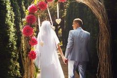 Uma vista de trás em um par do casamento que anda de um altar Imagem de Stock