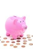 Uma vista de um banco piggy cor-de-rosa e de muitas moedas Fotografia de Stock Royalty Free