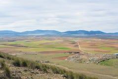 Uma vista de um monte aos campos, às explorações agrícolas e às montanhas perto de Consuegra Fotos de Stock Royalty Free