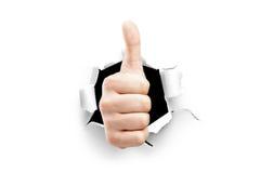 Uma vista de um polegar acima através de um furo no papel Foto de Stock Royalty Free