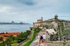 Uma vista do centro histórico de Havana e da terraplenagem de Malecon da fortaleza do EL Morro, através do passo do mar imagens de stock