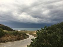 Uma vista do mar e da estrada no primeiro plano antes da tempestade com as nuvens cinzentas escuras que aproximam a ilha fotos de stock