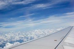 Uma vista embora uma janela do avião onde uma pode ver a asa e o céu nebuloso bonito Imagem de Stock Royalty Free