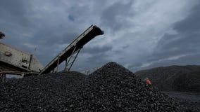Uma vista geral de um carvão que cai do transporte de correia na mina de carvão filme