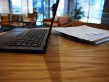 Uma vista lateral de um portátil aberto em uma tabela imagens de stock