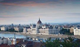 Uma vista que negligencia a cidade da construção do parlamento e Budapest húngaro e o rio Danúbio no por do sol cor-de-rosa, Hung Fotografia de Stock Royalty Free