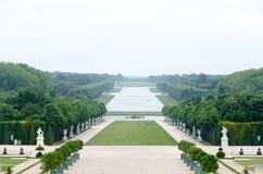 Uma vista só do parque de Versalhes, França A combinação geométrica de árvores verdes, de áreas da grama e das estátuas brancas fotografia de stock