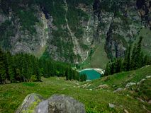 Uma vista superior da represa no pé de montanhas enormes imagem de stock royalty free