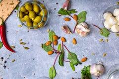 Uma vista superior de ingredientes da salada Esverdeie azeitonas enchidas em uma bacia de vidro ao lado das porcas da amêndoa e d Fotografia de Stock Royalty Free