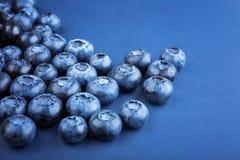 Uma vista superior de mirtilos doces Mirtilos em um fundo azul Bagas sas e saborosos Ingredientes para petiscos do vegetariano Imagens de Stock