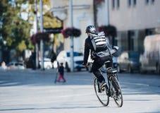 Uma vista traseira do correio masculino da bicicleta que entrega pacotes na cidade Copie o espaço fotos de stock royalty free