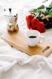 Uma xícara de café, café nas placas de madeira, um ramalhete de rosas vermelhas em um fundo branco Imagens de Stock