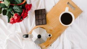 Uma xícara de café, café nas placas de madeira, um ramalhete de rosas vermelhas em um fundo branco Foto de Stock