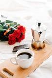 Uma xícara de café, café nas placas de madeira, um ramalhete de rosas vermelhas em um fundo branco Fotos de Stock Royalty Free