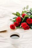 Uma xícara de café, café nas placas de madeira, um ramalhete de rosas vermelhas em um fundo branco Imagens de Stock Royalty Free