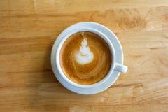 Uma xícara de café com arte do latte em um copo branco em vagabundos de madeira da tabela Imagem de Stock