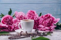 Uma xícara de café com as peônias cor-de-rosa luxúrias em um fundo azul imagens de stock royalty free