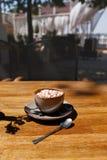 Uma xícara de café com marshmallows em um fundo de madeira da tabela Uma bebida do cacau em um copo da porcelana com uma colher d fotografia de stock royalty free