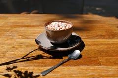 Uma xícara de café com marshmallows em um fundo de madeira da tabela Uma bebida do cacau em um copo da porcelana com uma colher d fotos de stock